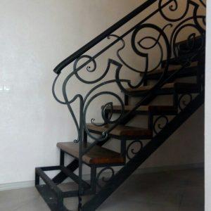 Лестница с коваными ограждениями и деревянными ступенями